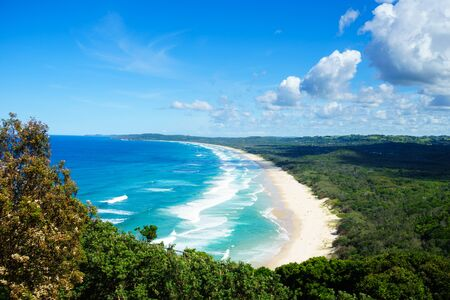 Horizontal view looking down onto Tallow Beach in Byron Bay.  The Pacific Ocean is a lovely blue turquoise with white waves. The sand is golden and the beach is surrounded by the green of Arakwai National Park. Stock Photo