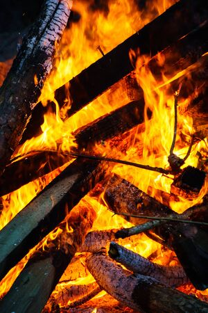 Burning fire with interlaced planks of wood forming triangle patterns. Stock Photo