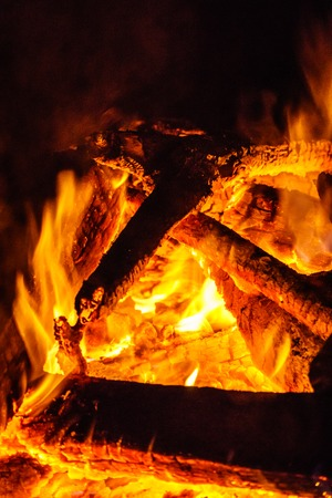 Red hot coals and flames at the base of a burning wood fire.