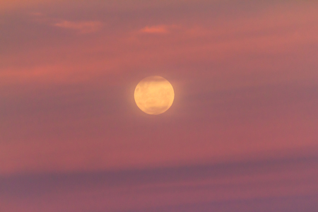 A yellow full moon rising into pink sunset clouds