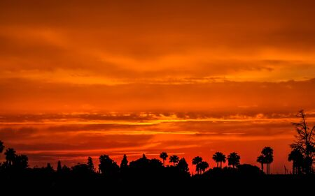 Deep orange sky as the sun sets over the city of Marrakesh in Morocco Stock Photo