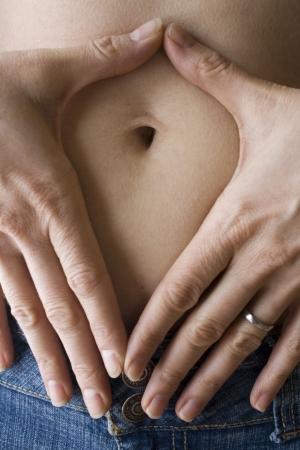bloating: Close up of womans belly button framed by hands