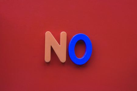The word 'no' spelled in children's magnetic letters on a red background Фото со стока - 6250232