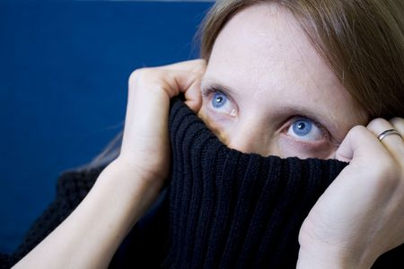 is embarrassed: Girl with blue eyes covering her face with a sweater