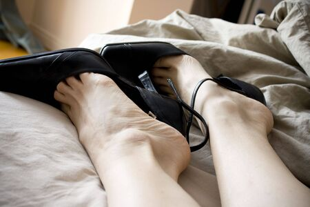 Woman feet in heels on a messy bed Stock Photo - 6644742