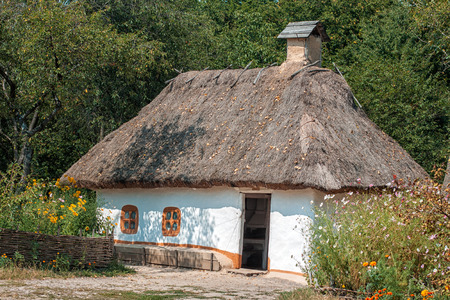 Old house with a thatched roof with a garden stands in the village