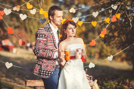 Newlyweds standing embracing in autumn park and hold a cup with a drink in hands