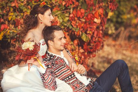 Portrait of bride and groom in autumn park they sit on the grass in autumn park bride groom hugging