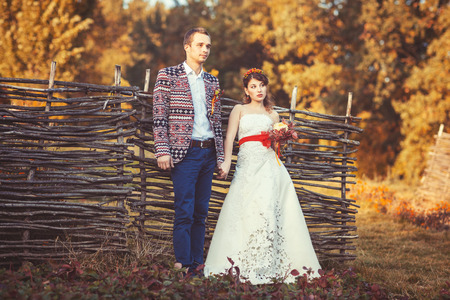 far away look: Bride and groom standing near the wicker fence holding hands and look far away
