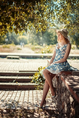 parapet: Beautiful girl sitting on a stone parapet in the park and misses. Stock Photo