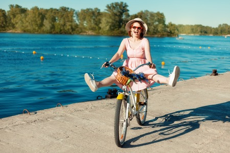 legs apart: Portrait of a beautiful girl in a hat and glasses on a bicycle. She rides a bicycle on the riverbank with her legs apart. Girl laughs