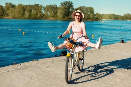 legs apart: Retrato de una hermosa ni�a en un sombrero y gafas en una bicicleta. Ella monta una bicicleta en la orilla del r�o con las piernas separadas. Risas de chicas