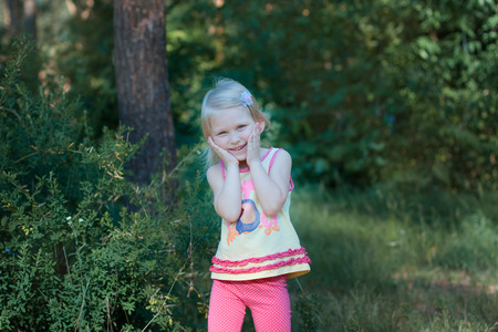 bowed head: Little beautiful blonde girl standing in the forest. She girl put her face in her hands and bowed her head, she laughs
