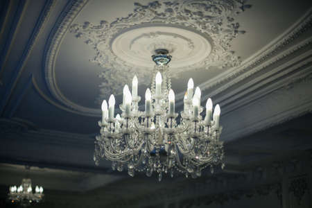 Beautiful antique crystal chandelier hangs from the ceiling in the shadows