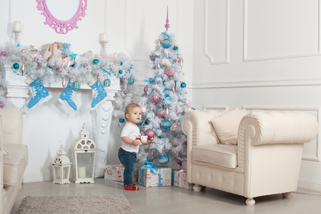 baby near christmas tree: Beautiful baby girl near a Christmas tree with presents and holding a toy