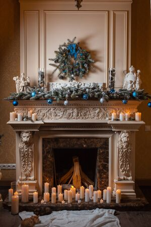 Christmas fireplace with candles and decorations. Kittens near the fireplace