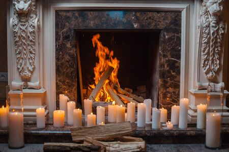 hearth and home: In a fireplace fire burns. Near the fireplace is a lot of burning candles