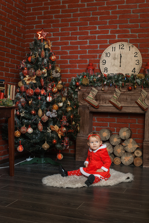 baby near christmas tree: Baby girl dressed as Santa Claus sits near a Christmas tree