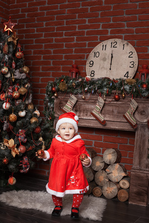 baby near christmas tree: Baby girl dressed as Santa Claus stands near a Christmas tree and holding Christmas balls