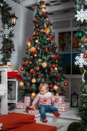 baby near christmas tree: Baby girl is sitting near the Christmas tree with presents