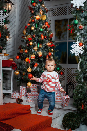 baby near christmas tree: Baby girl standing near the Christmas tree and holding a toy Stock Photo