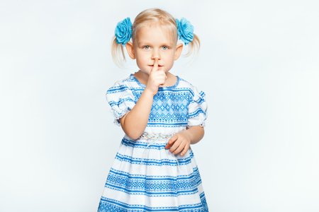 shh: Little beautiful blond girl on a white background making shh