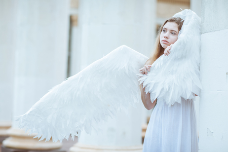 angel alone: Beautiful girl in a white dress wrapped in a wing Stock Photo