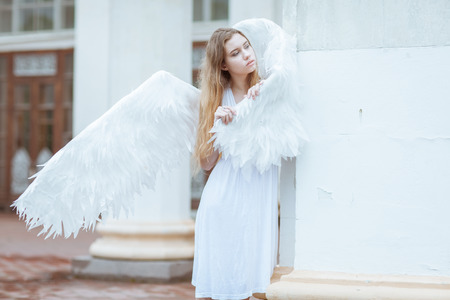 angel alone: Young woman with angel wings standing near a column and looking away Stock Photo