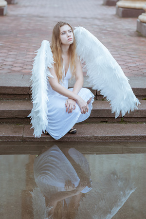 water wings: Girl angel with white wings sitting on the steps near the water Stock Photo