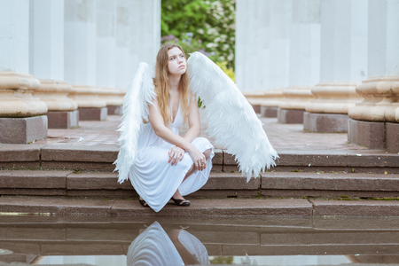 water wings: Girl with white wings sitting near the water among the columns Stock Photo