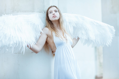 angel alone: Beautiful girl with white wings standing near a white wall