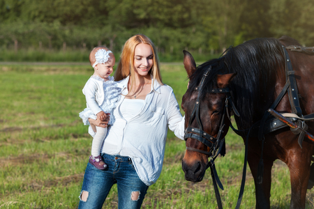 green life: Mama and her little daughter standing in a meadow near a horse