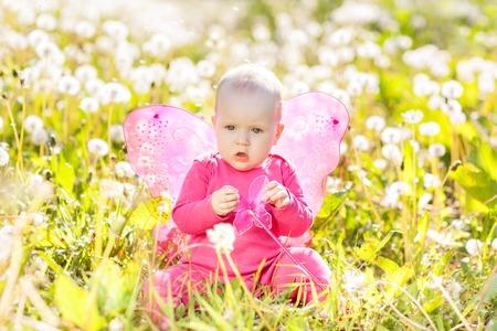 Child girl sitting among dandelions