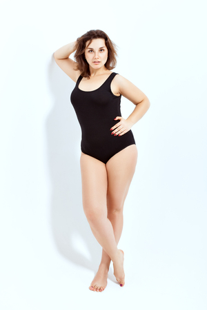 Portrait of a beautiful full-length girl in a black swimsuit on a white background. Stock Photo