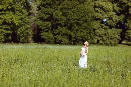 Pregnant woman standing in the grass. She closed her eyes and looked up. Reklamní fotografie