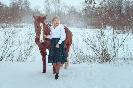 Beautiful woman is standing next to a horse in a winter park. 版權商用圖片