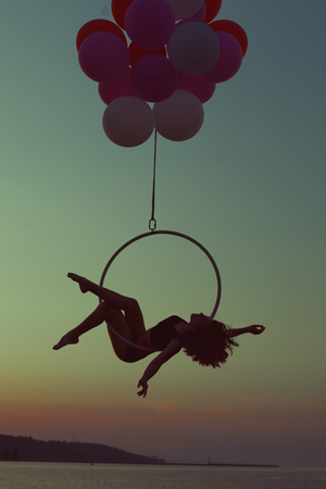 Acrobat girl doing acrobatic tricks on a circle on the setting sun.