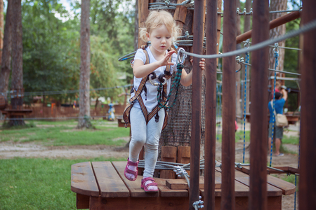 Little girl in the equipment overcomes the obstacle in the rope park.