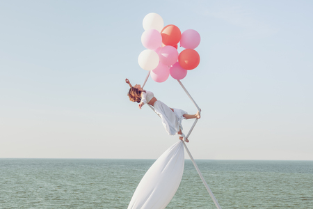 Young woman does tricks in the air on white canvases over the sea. Stock Photo