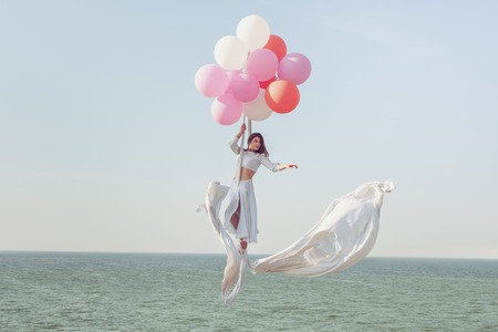 Young woman flying in the air by balloons over the sea.