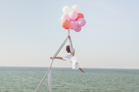Young woman hovers in the air on balloons above the sea.