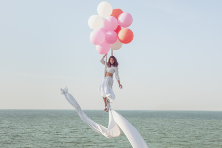Young woman in a white suit hovers in the air in balloons.