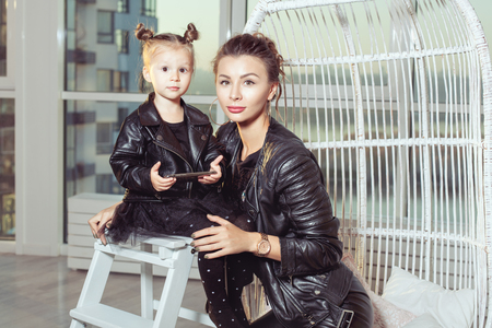 Portrait of a young mother and her daughter in black clothes. Banque d'images - 117954516