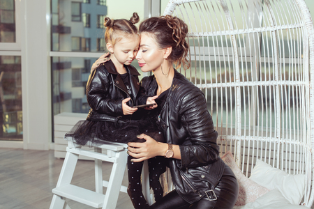 Portrait of a young mom and her daughter in black leather jackets. Banque d'images - 117954519