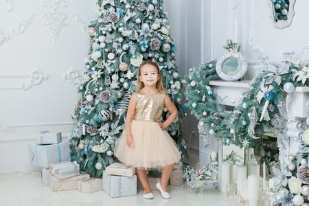 Little girl stands near the Christmas tree in the room. Banque d'images - 117954525