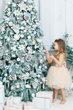 Little girl in beautiful dress decorates the Christmas tree. Banque d'images - 117954526
