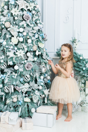 Little girl in a beautiful dress stands near a Christmas tree. She is surprised.