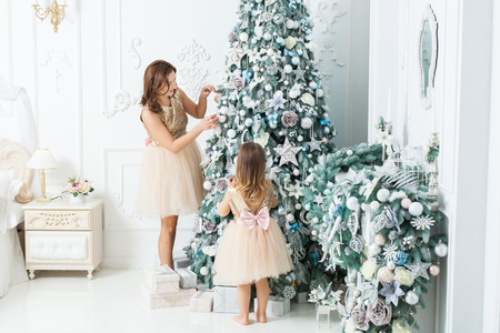 Mom and daughter decorate Christmas tree with toys. Banque d'images - 117954535