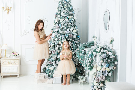 Young beautiful woman with her daughter decorate the Christmas tree. Banque d'images - 117954536