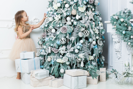 Little girl in a beautiful dress hangs decorations on the Christmas tree.